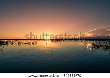 Colorful Sunset on a peaceful lake. Warm colors sunset on water, Sri Lanka - stock photo