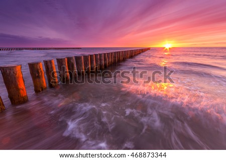 Colorful sunset on Baltic sea beach with wooden groyne