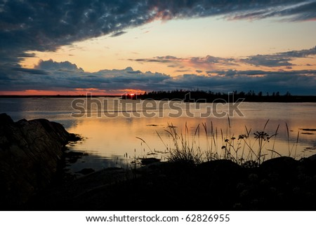 Colorful sunset on the coast of a small rocky island of White sea.