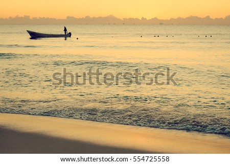 Colorful sunset on the tropical beach with beautiful sky, clouds, boat and soft waves. Photo from Playa Del Carmen, Riviera Maya, Mexico.