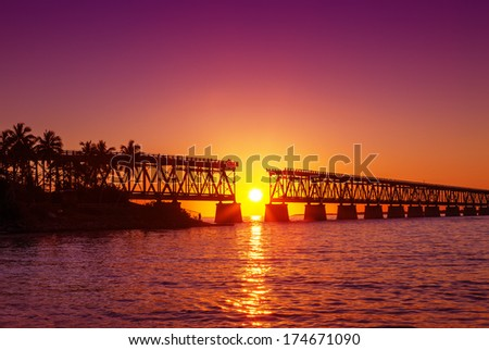 Colorful sunset or sunrise with broken bridge - stock photo