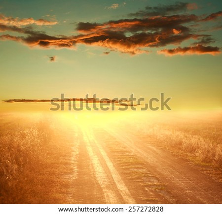 Colorful sunset over country road on the background of dramatic sky - stock photo