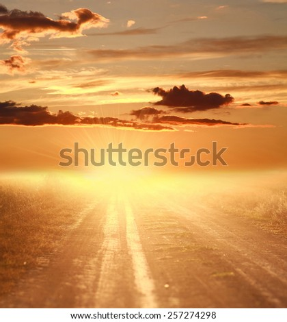 Colorful sunset over country road on the background of dramatic sky and blinding rays of light - stock photo