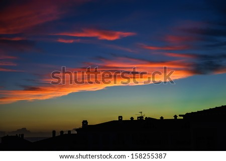 Colorful sunset over houses silhouettes in small portugal village