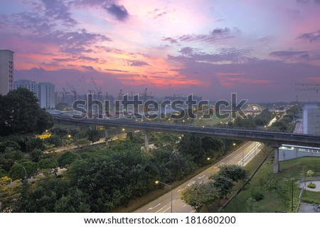 Colorful Sunset Over Punggol Housing Estate with Light Rail Track and Freeway in Singapore - stock photo