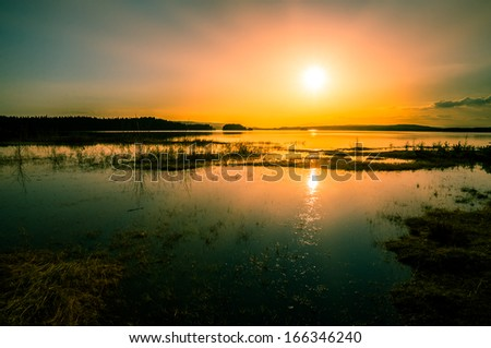 colorful sunset over the flooded lake - stock photo