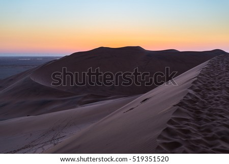 Colorful sunset over the Namib desert, Namibia, Africa. Scenic sand dunes in backlight in the Namib Naukluft National Park, Swakopmund.