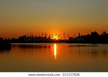 Colorful sunset over tranquil water surface.