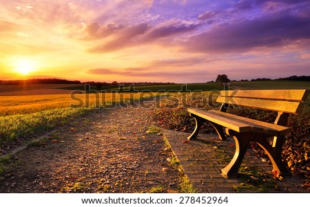 Colorful sunset scenery in rural landscape with a bench and a path in the foreground, gold fields and dramatic vivid sky in the background - stock photo