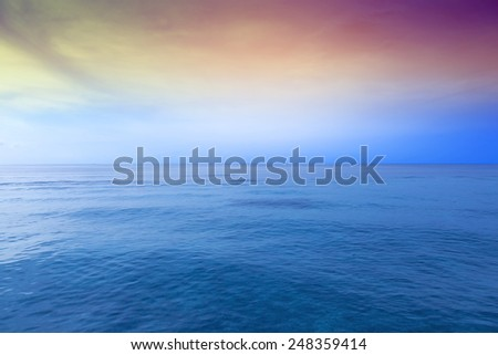 Colorful sunset sky over wide blue ocean - stock photo