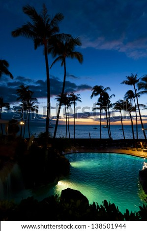 Colorful sunset through palm trees overlooking a pool on  Maui, Hawaii, USA - stock photo