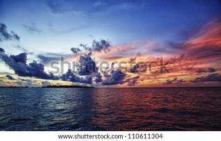 Colorful sunset with clouds over the ocean in Maldives
