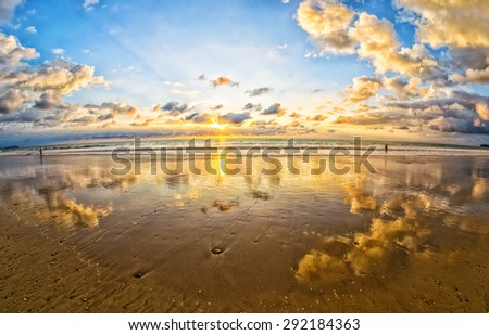 Colorful sunset with reflections at tropical beach