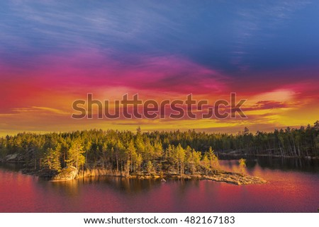 Colorful surrealistic landscape with dramatic beautiful vivid sky at sunset golden hour. Nature of Northern Europe or America.