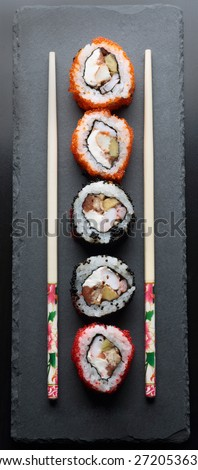 colorful sushi with chopsticks on a dark background - stock photo