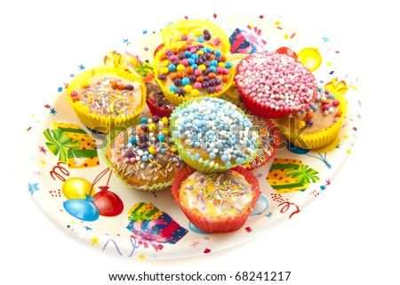 Colorful sweet cup cakes on a decorated plate isolated over white - stock photo