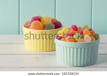 Colorful sweet jellies with sugar in two yellow and turquoise classic white-ware baking bowls on a white wooden table with a robin egg blue background. Vintage look. - stock photo
