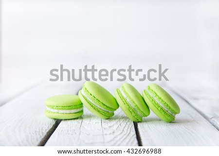 Colorful sweet macaroons on vintage wooden background.