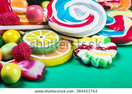 Colorful sweets and candies on a green background. focus on lollipops
