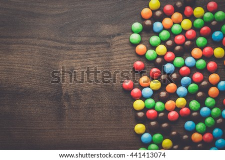 colorful sweets on the brown wooden table background - stock photo
