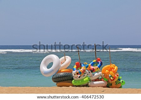 Colorful Swim Ring Hanging on Wooden Poles on the Beach at Sanur Beach, Bali, Indonesia. - stock photo