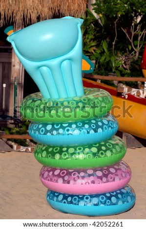 Colorful swimming rings are creatively organized and held in place by sticking an inflated floating raft in center. - stock photo
