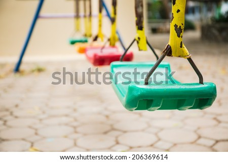 Colorful swings and rusty iron chain on cement block floor background - stock photo