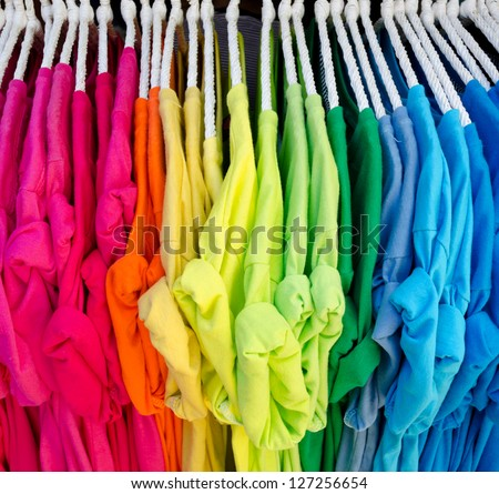 Colorful t-shirt on hangers - stock photo