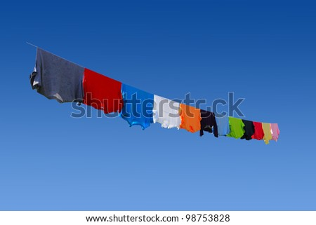 Colorful T-shirts hanging on clothesline in summer time - stock photo