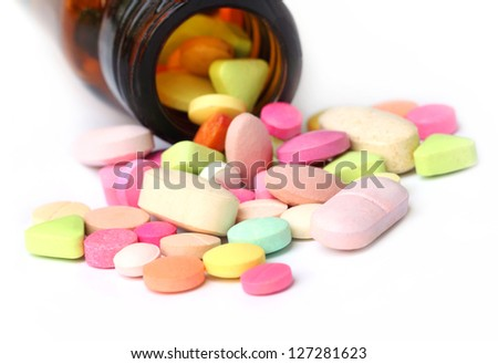 Colorful tablets spilled out bottles
