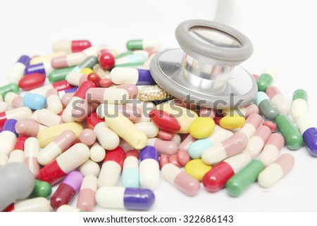 Colorful tablets with capsules and pills on white background