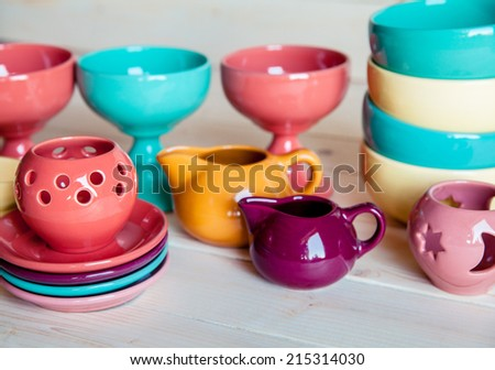 colorful tableware on a wooden background - stock photo