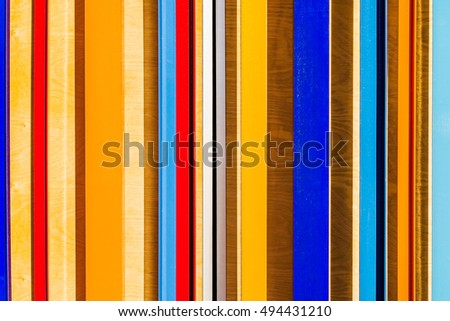 Colorful texture of vertical bars or planks made of wood, plywood and metal. Rainbow of colors and geometry of lines brings to memory bar code. Texture or background