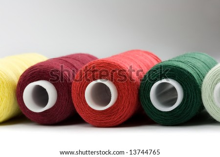 Colorful thread reels on white background