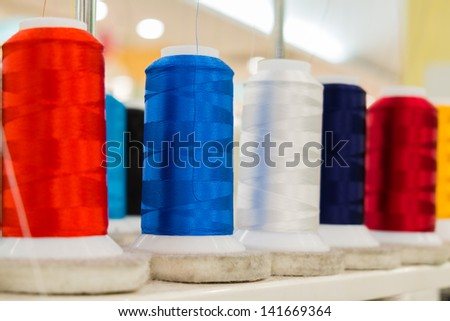 Colorful Thread roll on sewing machine in factory - stock photo