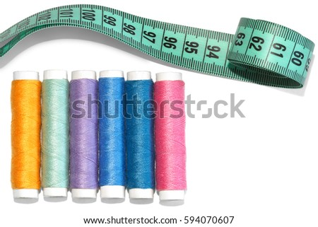 Colorful thread spools and tape measure isolated on white