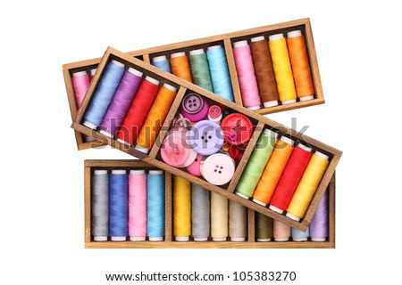 Colorful threads and buttons in wooden box - stock photo