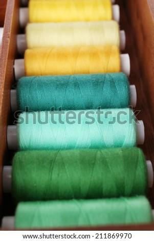 Colorful threads for needlework in wooden box close up - stock photo