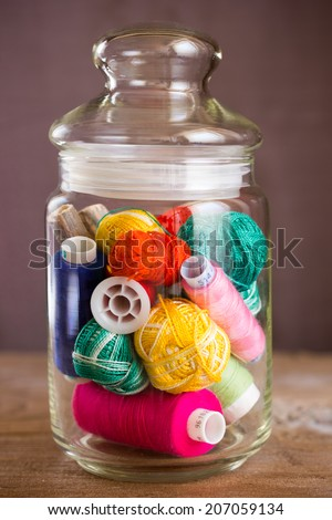 Colorful threads in glass jar