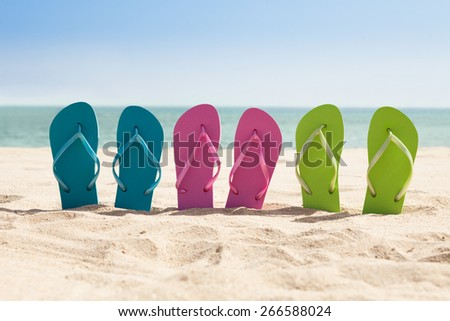 Colorful Three Pairs Of Flip-flops On Beach - stock photo