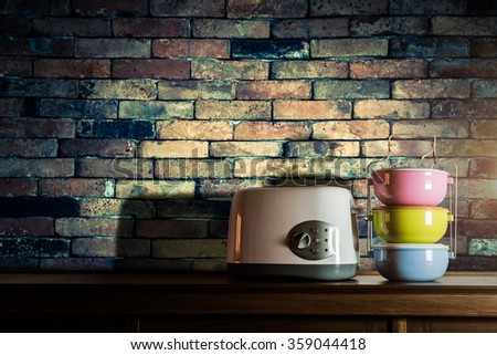 Colorful tiffin carrier and toaster on wooden cupboard with vintage brick wall background against warm light - stock photo