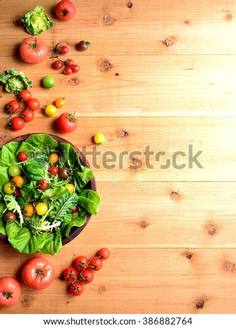 Colorful tomatoes and mesclun greens salad on the wooden back ground