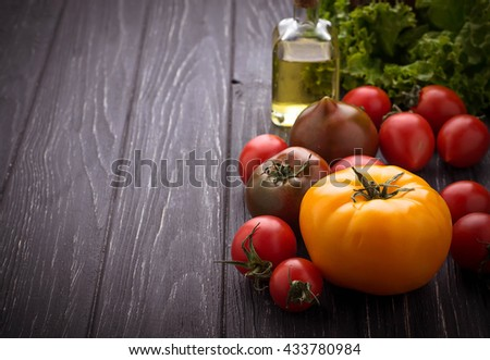 Colorful tomatoes on black background. Selective focus