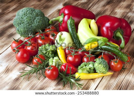 Colorful  tomatoes, pepper and mushrooms on wooden background - stock photo