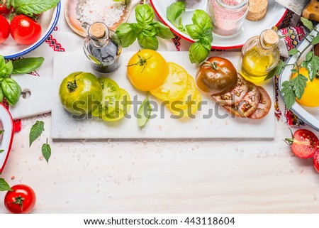 Colorful tomatoes salad ingredients on white marble cutting board and white wooden background, top view, border - stock photo