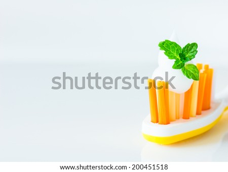 Colorful tooth brush with tooth paste and fresh mint leaf. Selective focus. Copyspace for your text. - stock photo