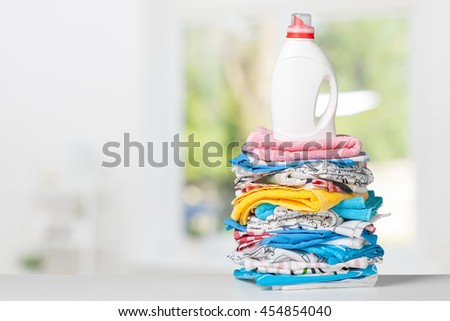 Colorful towels and liquid laundry detergent - stock photo