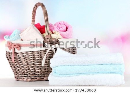 Colorful towels in basket, on table, on bright background - stock photo