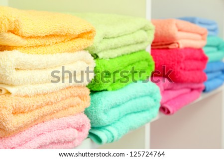 colorful towels on shelves in bathroom - stock photo