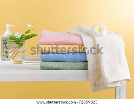 Colorful towels on wooden shelf - stock photo